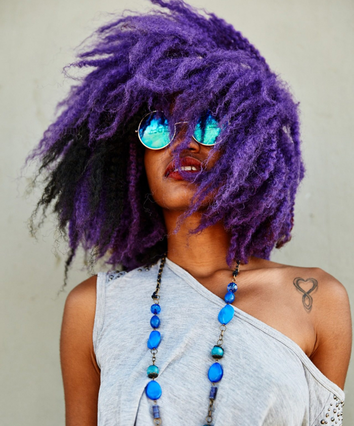 Afro american woman with purple hair and blue sunglasses