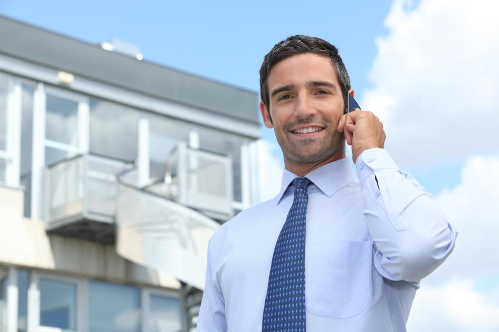 Man landlord with tie smiling and talking on the phone in front of his new property