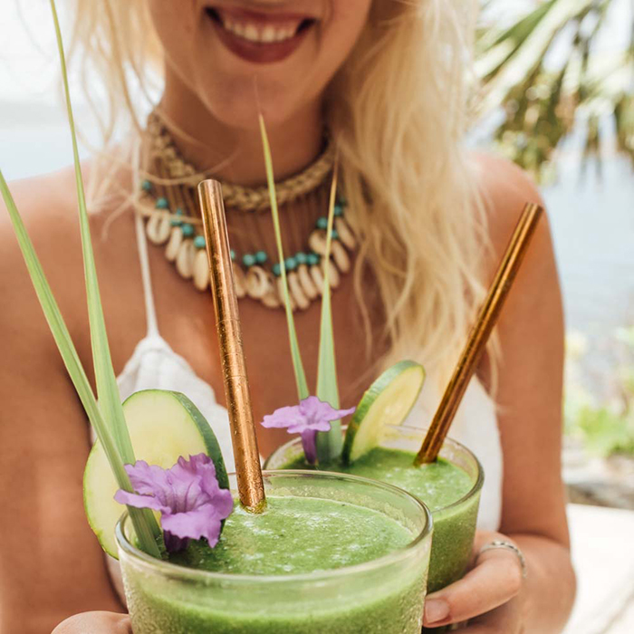 Woman holding two smoothies with plastic free straws