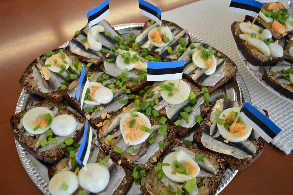 Sprats on slices of rye bread decorated with boiled eggs and Estonian flags