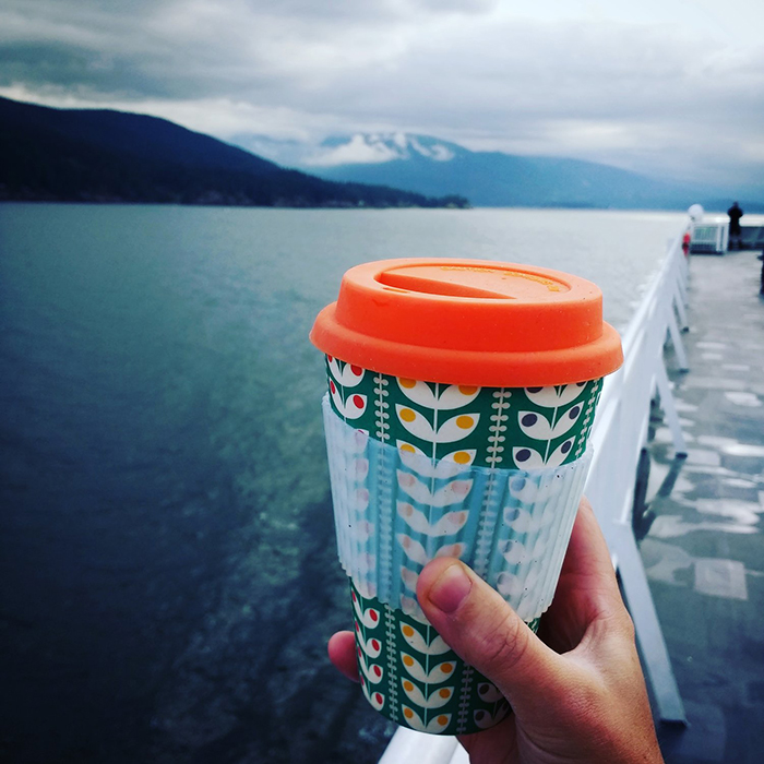 Person holding reusable travel mug with a nice ocean view behind