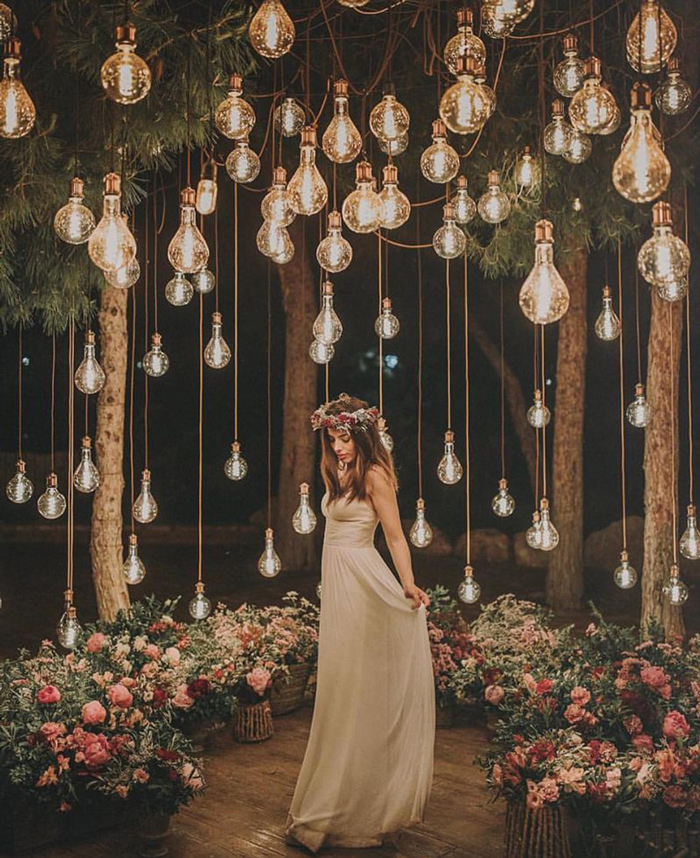 Bride standing surrounded by flowers and cozy lights