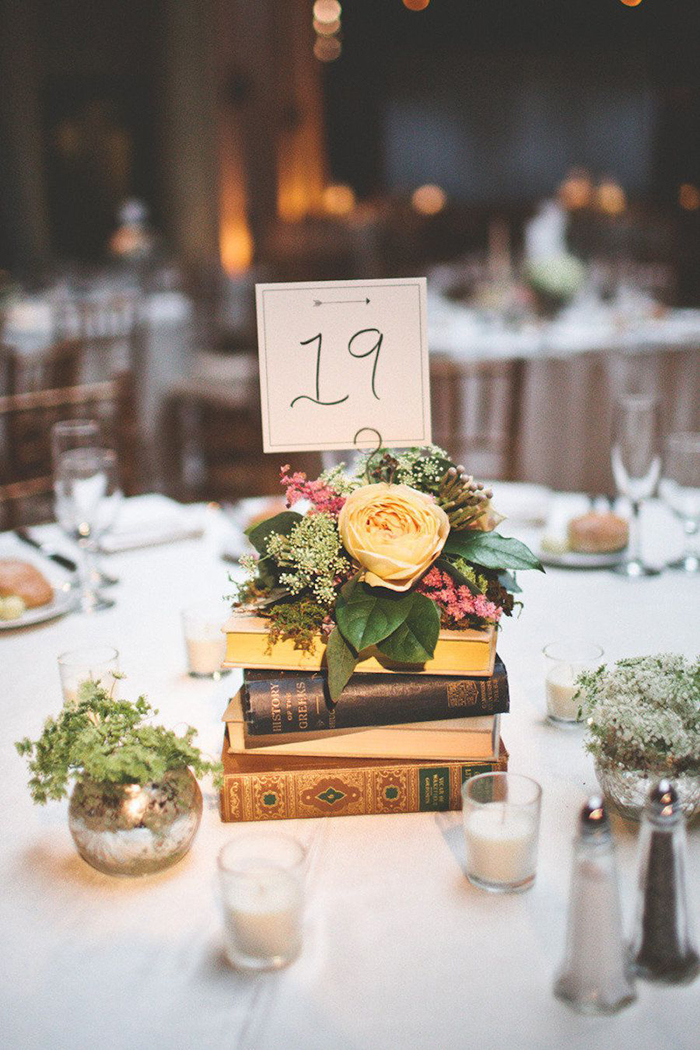 Unique wedding table decor with vintage books and flowers