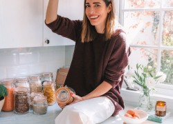Woman standing in the kitchen with jar full of paste zero waste kitchen