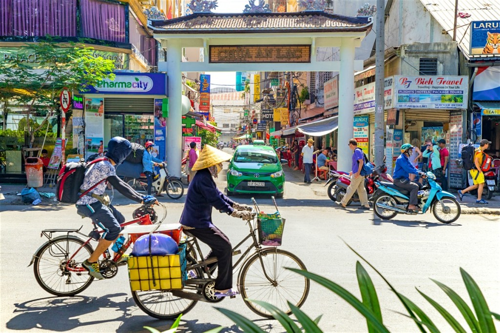 Crowded day in Vietnam with people cycling and shops around