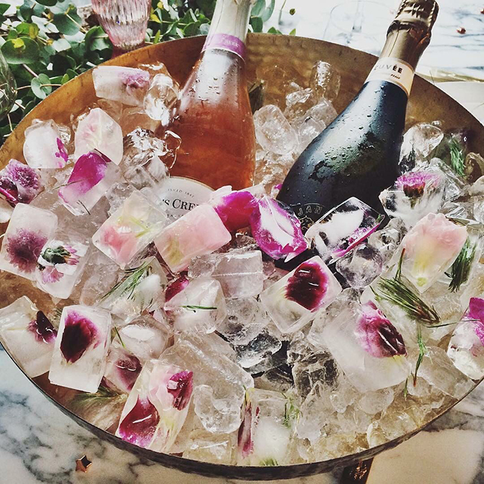 Flower filled ice cubes and two bottles of wine in them
