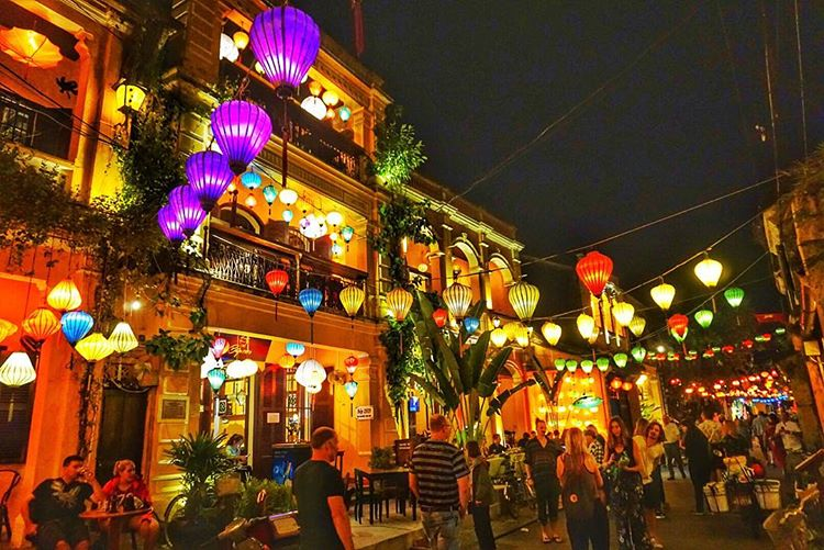Neighborhood in Hoi decorated with nice lanterns and people walking around