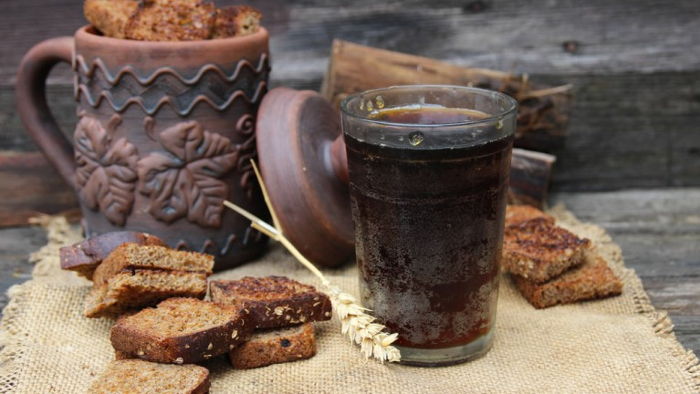 A glass full of kvass and rye bread around it