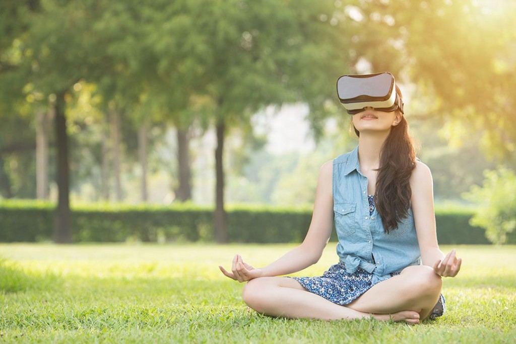 Girl sitting in a meadow but traveling to a different place through VR