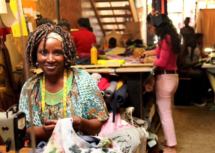 Afro american woman making Ethical clothes and smiling
