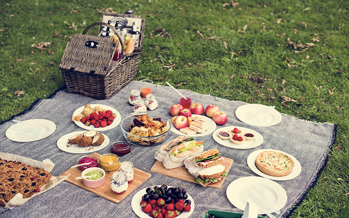 Picnic blanket full of different kinds of food like snacks and fruits