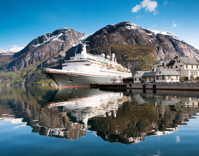Cruise ship on a port with small houses and mountains around