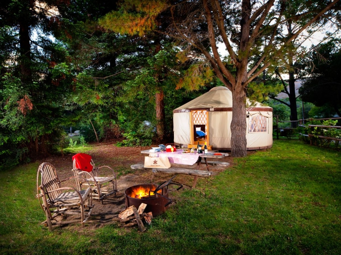 Hippie glamping tent with chairs in front and a campfire