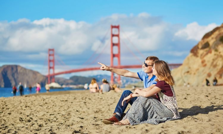 Couple enjoying the sun at the beach and the Golden gate Bridge in the bakcground