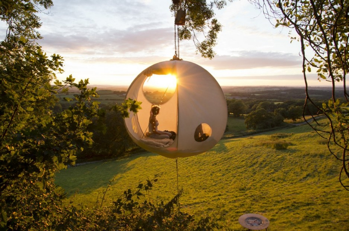 Person enjoying in a bubble shaped tent hanging on a tree with a nice view on the meadows