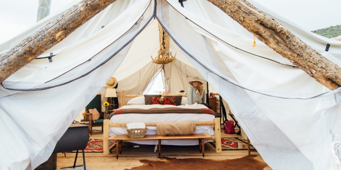 Luxury Glamping tent with wooden bed, vintage cushion, carpets and chandelier