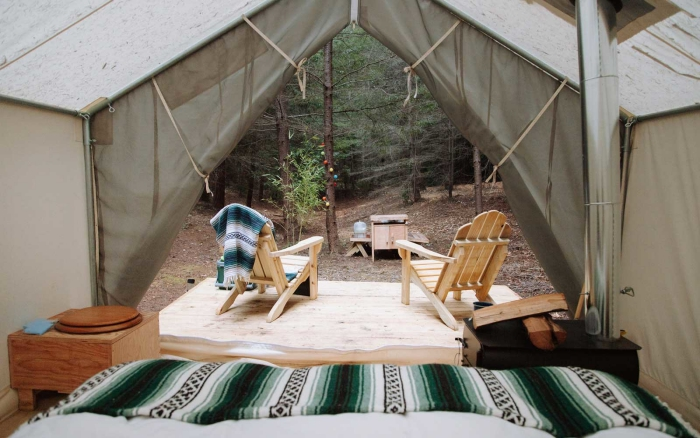 Fancy tent in the forest with two wooden chairs in front of it