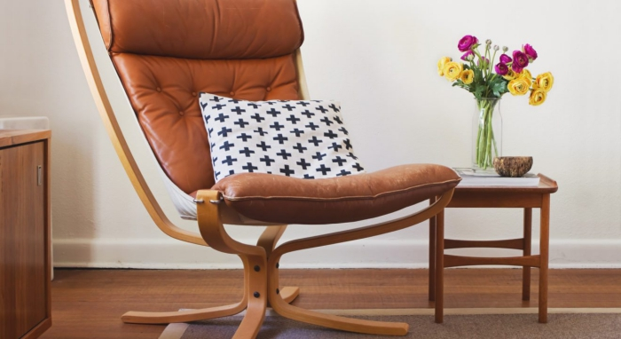 Mid Century Danish lounge designs reading chair with a cushion on it and flowers on a small table