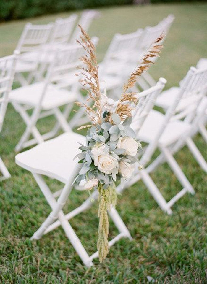 Flowers on every chair as a decor for a summer party