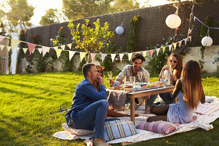 Group of friends having a summer party in the yard with drinks and food