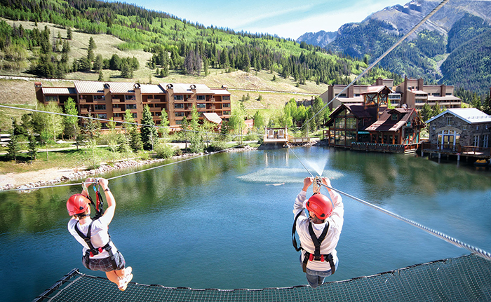 Two person on a zip line over a lake in Vail, Colorado