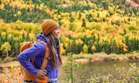 Autumn hiker girl outdoor in nature forest lake backpacking for camping travel trip. Happy Asian woman hiking outdoors with bag and hat, cold outerwear gear.