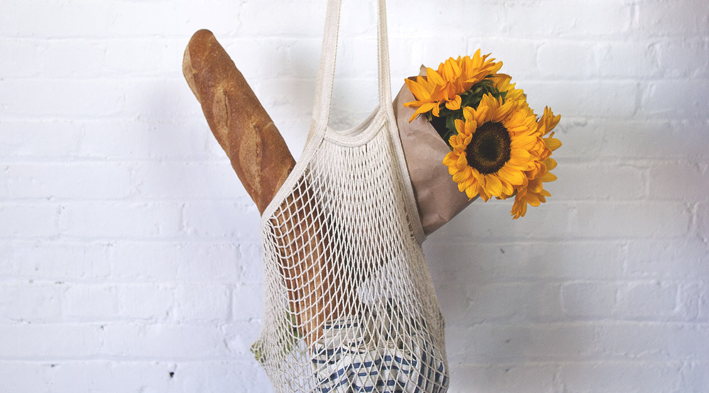 Reusable groceries bag with bread and flowers inside