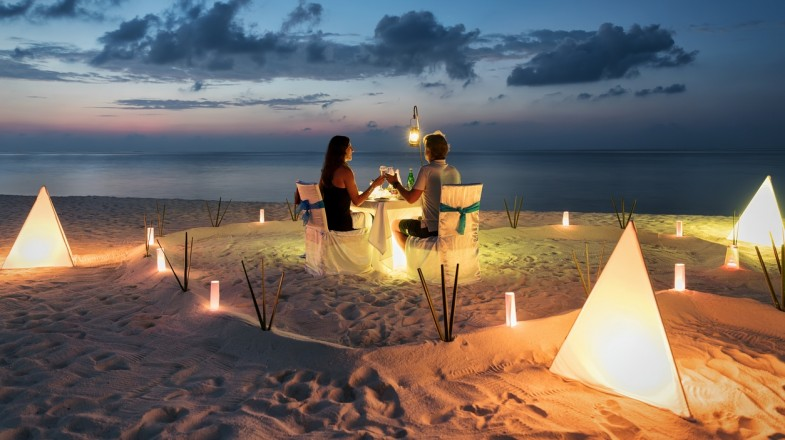 Couple enjoying a romantic dinner on a beach with candles around