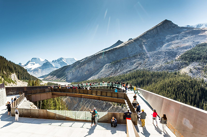 Tourists exploring Banff while walking on a bridge with a view on the mountains