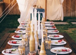 Summer party table decorated with candles in bottles and decorated jars instead of glasses