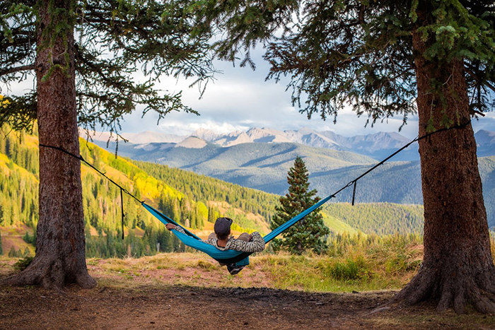 A person on a hammock with a view on meadows and mountains