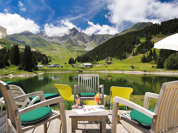 Wooden chairs and a table put in front of a small lake among the mountains in France