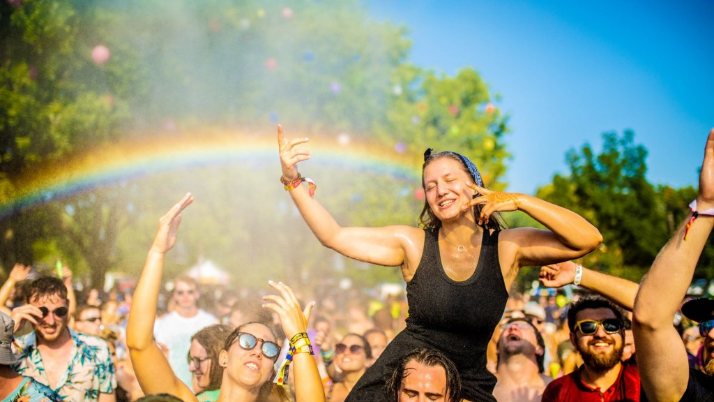 A girl on a man's shoulders dancing and a rainbow behind