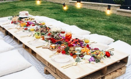 Short wooden table in garden full of food