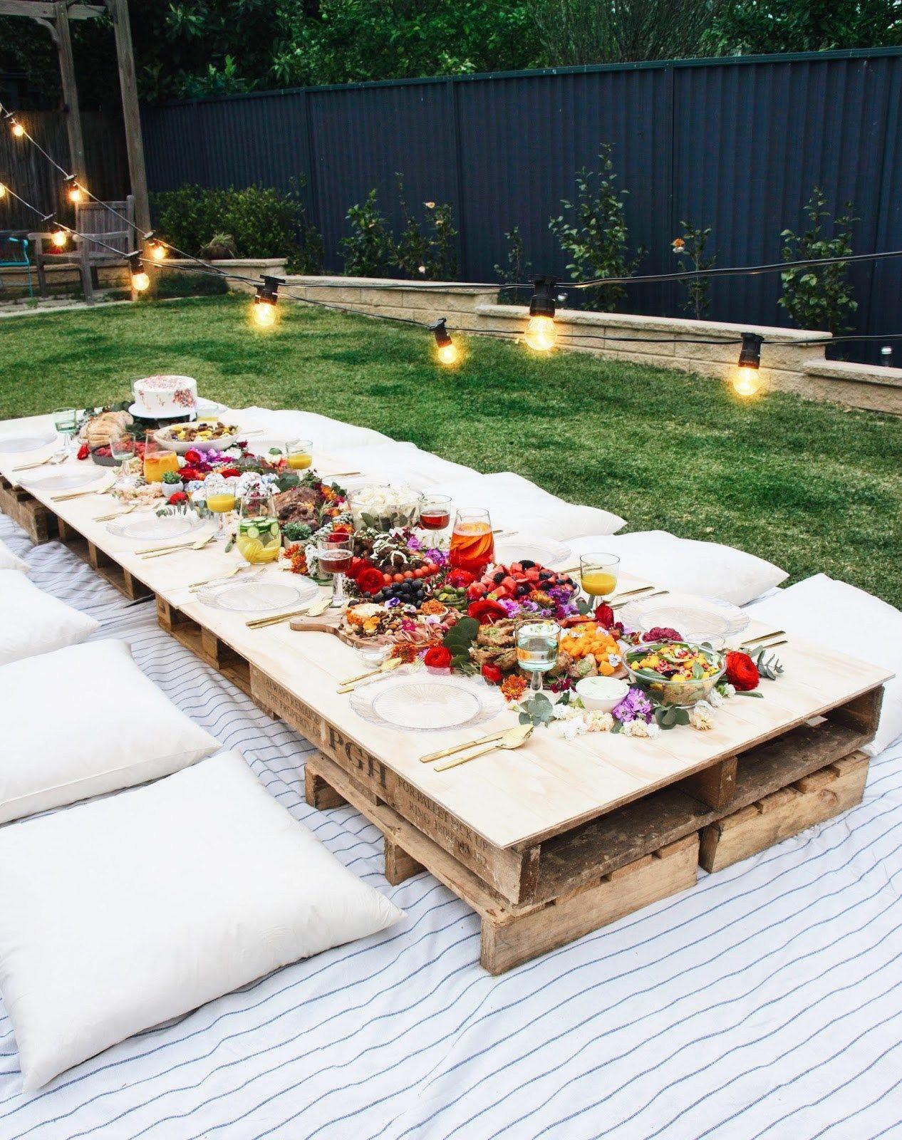 Short wooden table in garden full of food