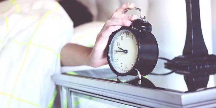 hand snoozing an alarm clock