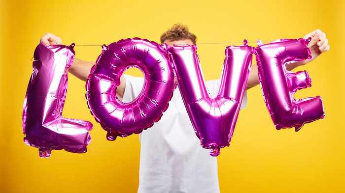 person holding large balloon with the word Love