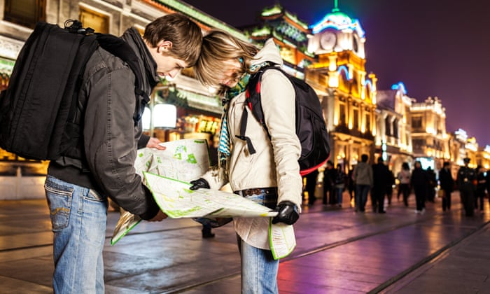 night photo of a couple looking at a map