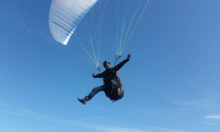 man flying in the air with a parachute