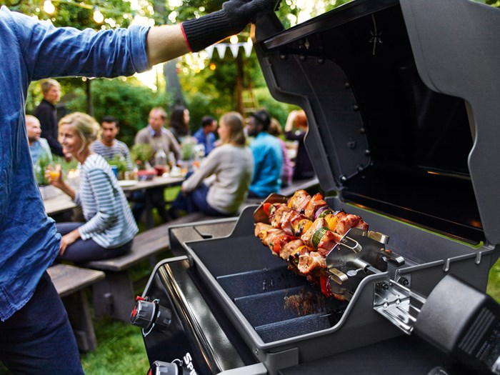 man opening a barbecue grill