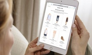 woman with a tablet choosing clothes from an online store