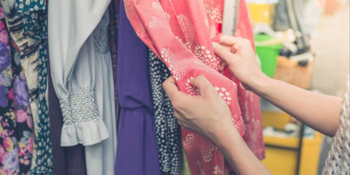 a hand touching a dress in a shop