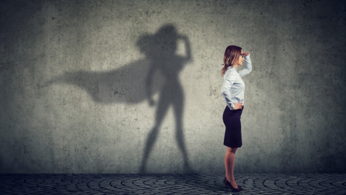 Woman with superwoman shadow on a wall