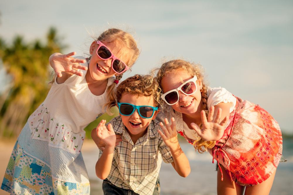 Three children waving and smiling at camera