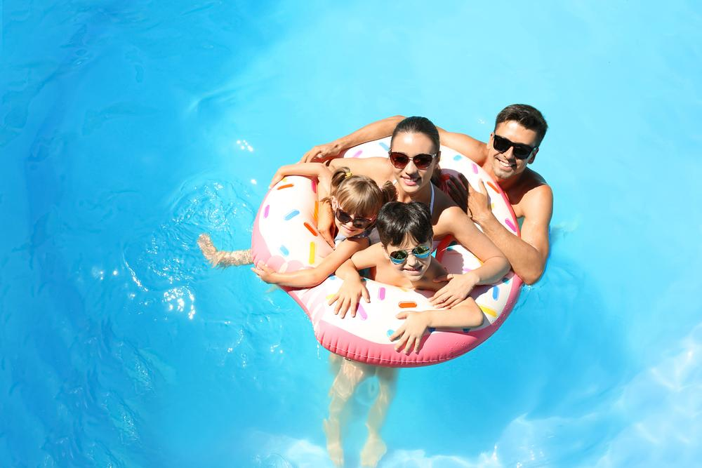 Family with two children in the pool celebrating summer