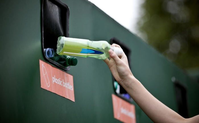 Hand throwing plastic bottle into a containter