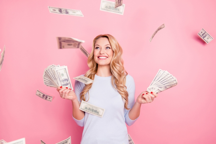 Money buy happiness young woman on a pink background with money