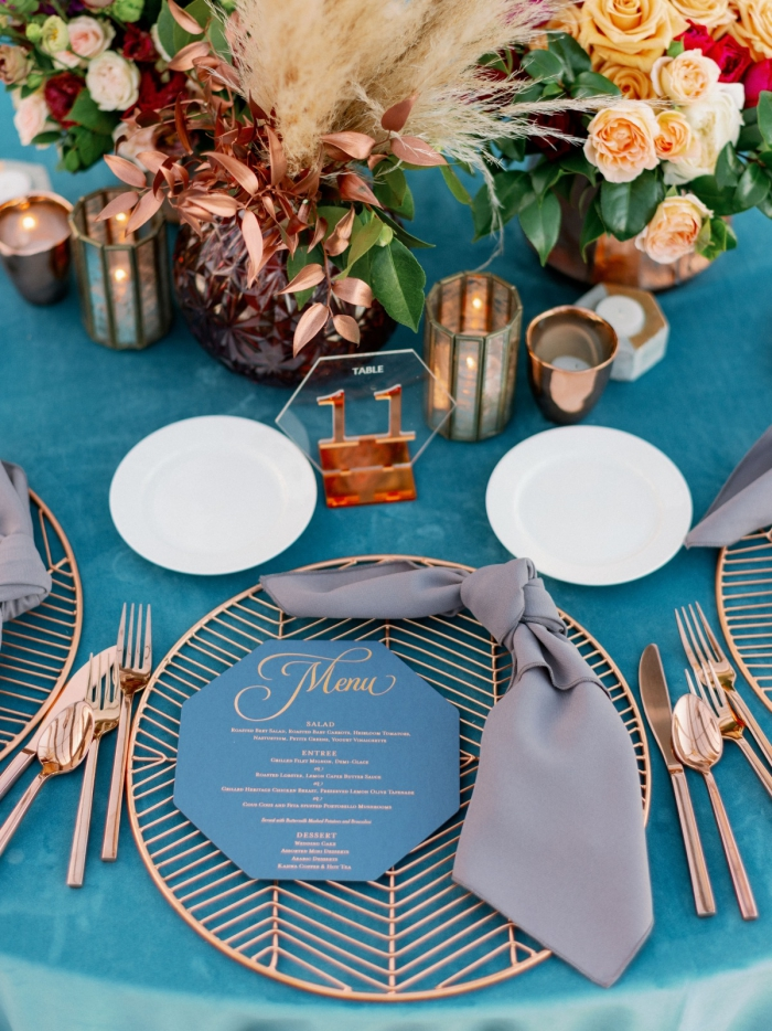 beautiful elegant wedding table decoration in gold and blue flower arrangements