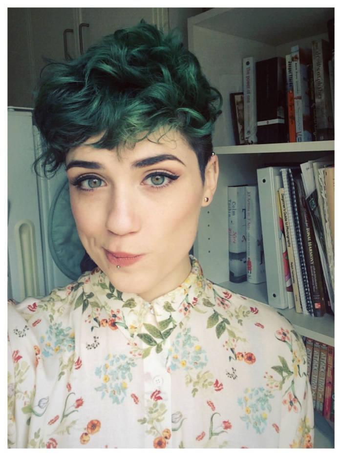 Young woman at home with light skin and eyes curly green pixie hairstyle