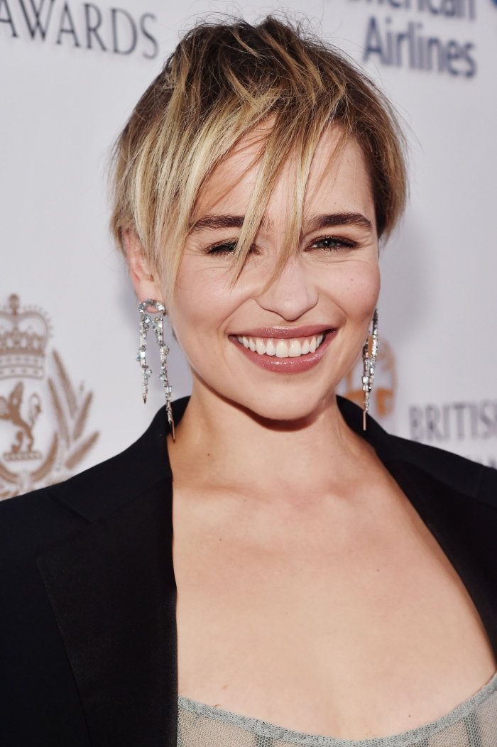 celebrity smiling on the red carpet short pixie hair long earrings black top